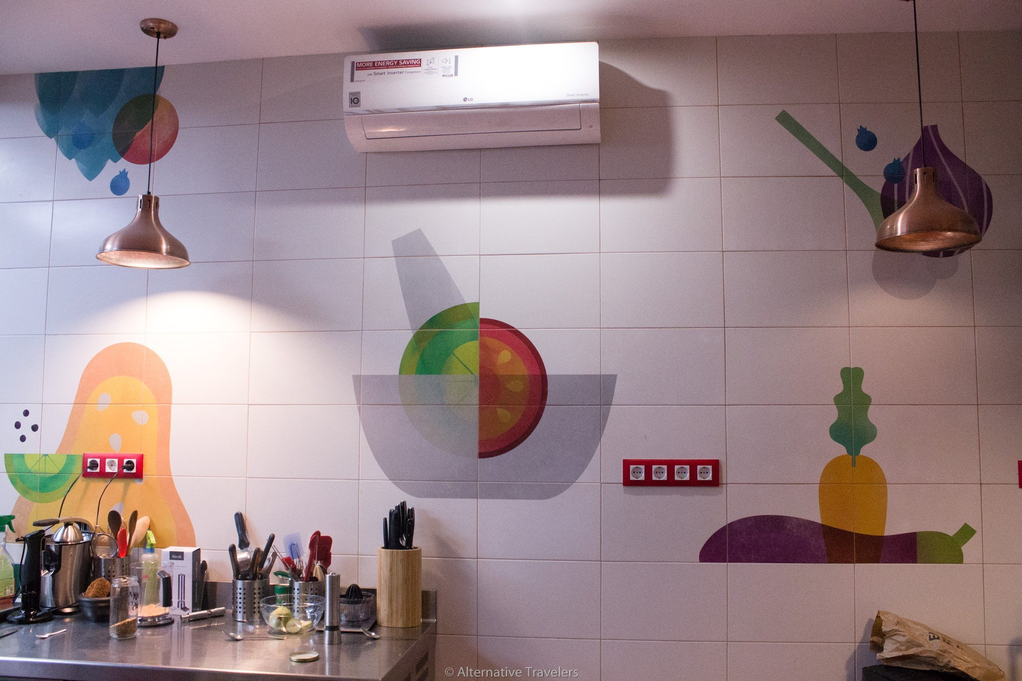 Kitchen and painted vegetables on the walls at Landareak, a vegan restaurant in Madrid
